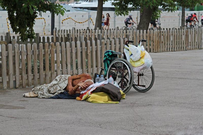 Uma pessoa deficiente desabrigada com uma cadeira de rodas que dorme no asfalto em Barcelona imagens de stock