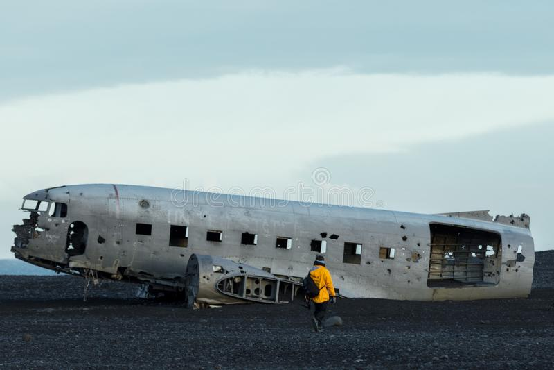 Uma pessoa em uma capa de chuva amarela que aproxima um avião deixado de funcionar velho em um campo foto de stock royalty free
