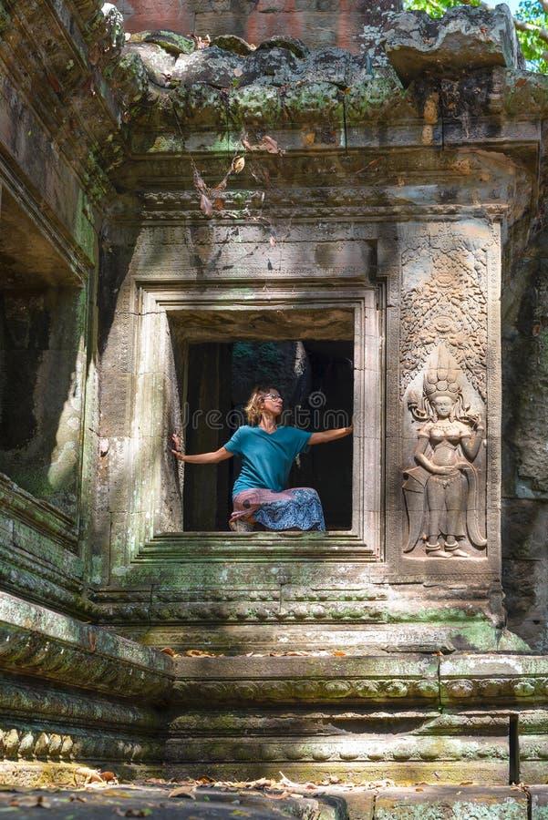 Uma pessoa em ru?nas de Angkor Wat, destino Camboja do curso Mulher na posi??o da ioga, esticando o p? e o bra?o aumentado, opini imagens de stock royalty free