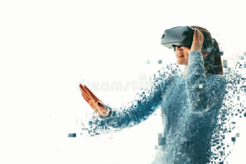 Uma pessoa em vidros virtuais voa aos pixéis A mulher com vidros da realidade virtual Conceito futuro da tecnologia fotografia de stock royalty free