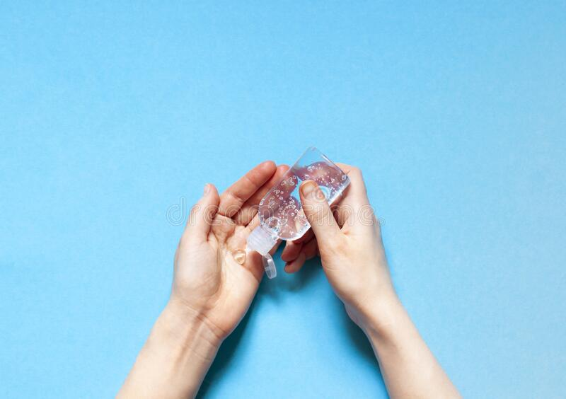 Uma pessoa está usando gel desinfetante manual antibacteriano transparente num frasco de plástico Coronavírus Covid- 19 medidas p fotografia de stock