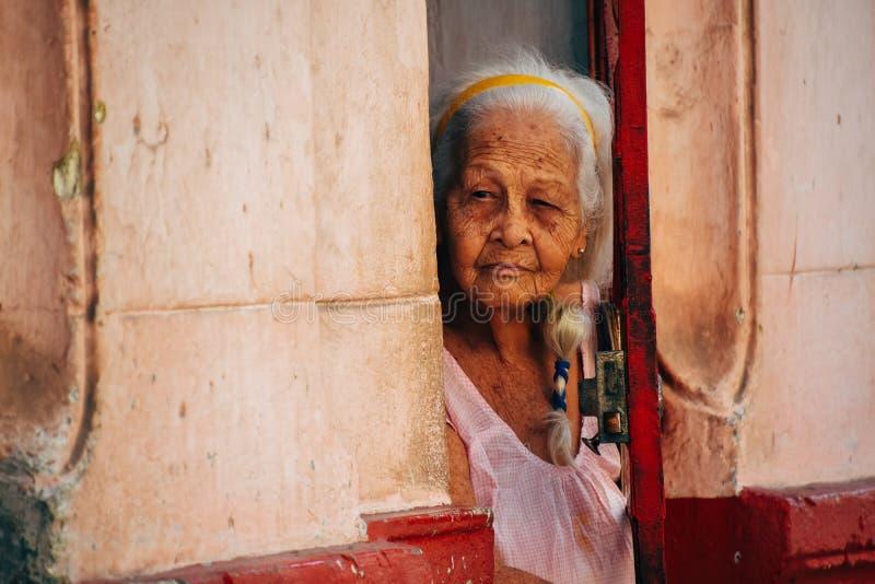 Uma pessoa idosa local olha fixamente fora de sua porta da rua em Havana, Cuba imagens de stock royalty free