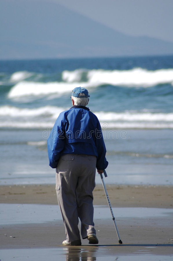 Uma pessoa idosa na praia imagem de stock