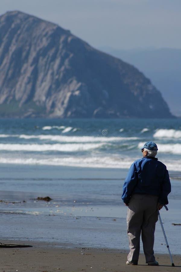 Uma pessoa idosa na praia fotografia de stock