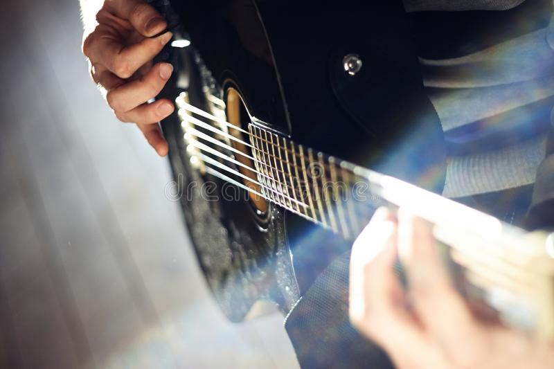 Uma pessoa joga uma guitarra lustrosa preta, ao guardar um mediador em suas mãos foto de stock