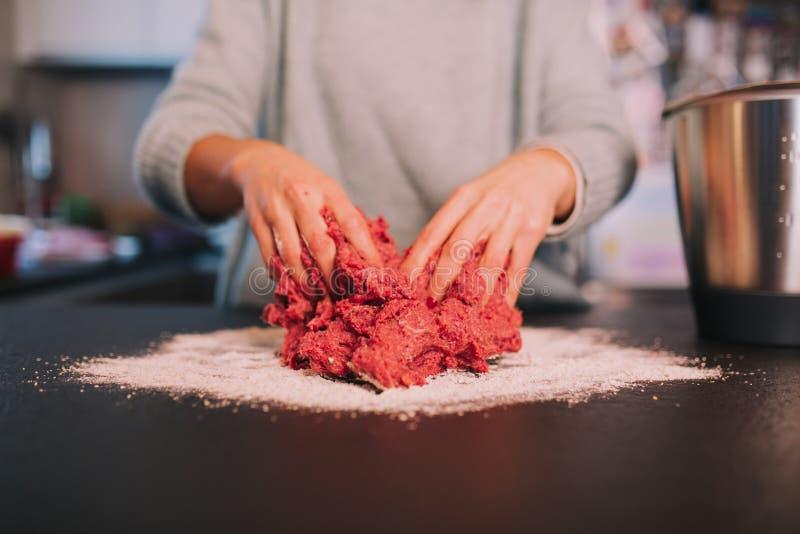 Uma pessoa que amassa a carne triturada fotos de stock