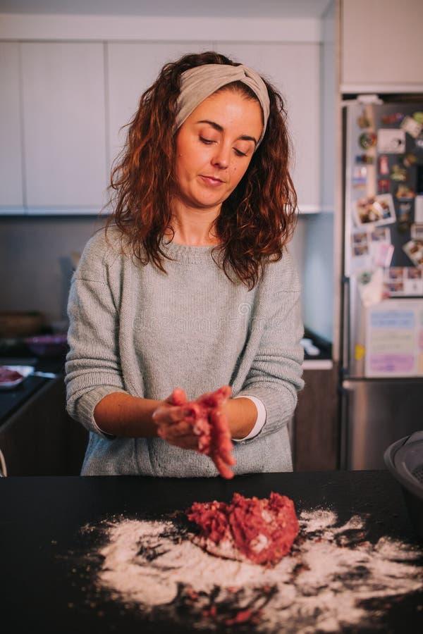 Uma pessoa que amassa a carne triturada fotografia de stock