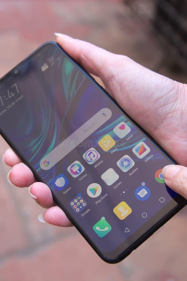 Uma pessoa que conduz um smartphone da empresa chinesa Huawei imagem de stock
