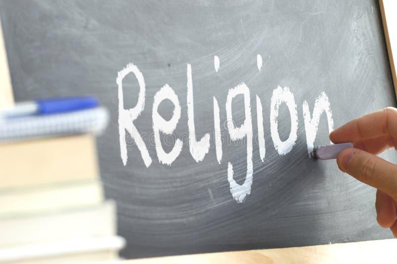 Uma pessoa que escreve a religião da palavra em um quadro-negro fotos de stock royalty free