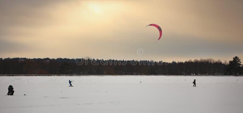 Uma pessoa que kiting com os papagaios coloridos no inverno na neve fotos de stock