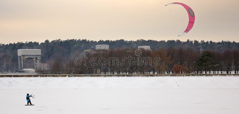 Uma pessoa que kiting com os papagaios coloridos no inverno na neve imagem de stock royalty free