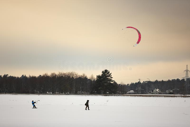 Uma pessoa que kiting com os papagaios coloridos no inverno na neve fotos de stock royalty free