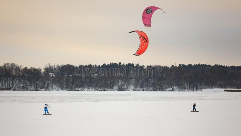 Uma pessoa que kiting com os papagaios coloridos no inverno na neve imagens de stock