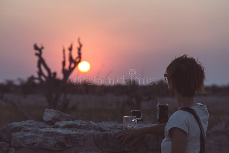 Uma pessoa que tem uma bebida e que olha o por do sol colorido no deserto de Namib, destino do curso em Namíbia, África Conceito  imagem de stock