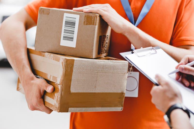 Uma pessoa que veste um t-shirt alaranjado e uma etiqueta do nome está entregando um pacote a um cliente, que esteja pondo sua as fotos de stock