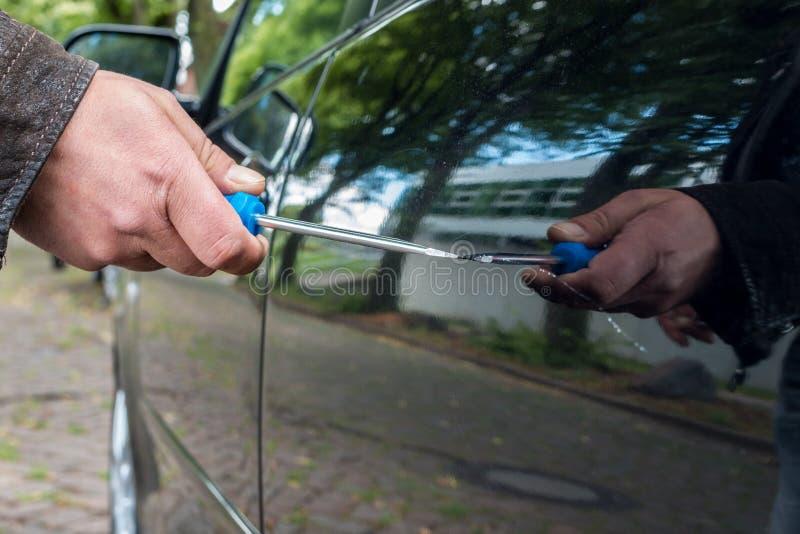 Uma pessoa risca a porta de carro em um carro com uma chave de fenda foto de stock
