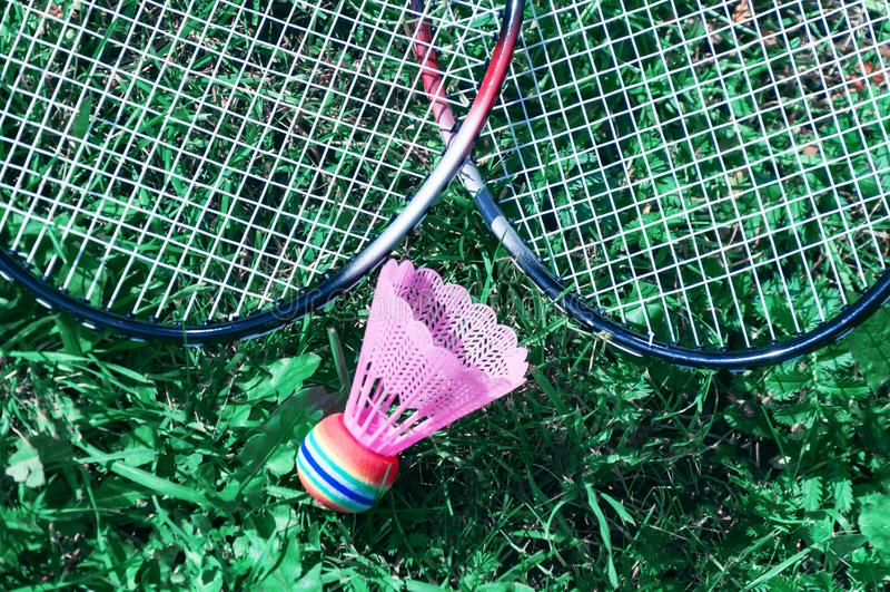 Uma peteca cor-de-rosa e uma raquete de badminton encontram-se na grama verde do gramado fotografia de stock