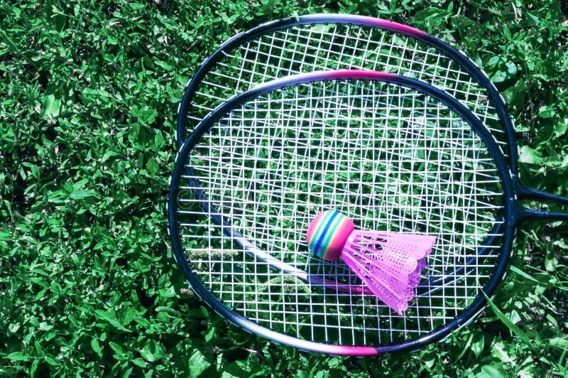 Uma peteca cor-de-rosa e uma raquete de badminton na grama verde do gramado fotografia de stock