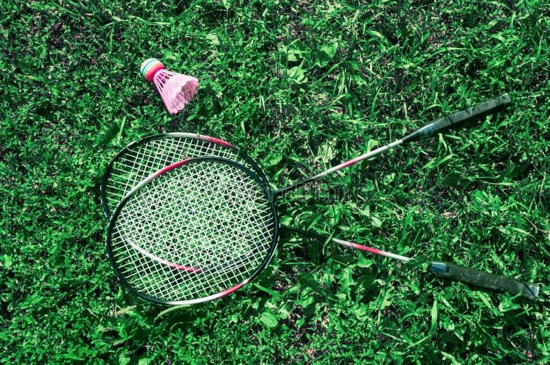 Uma peteca cor-de-rosa e uma raquete de badminton na grama verde do gramado imagem de stock