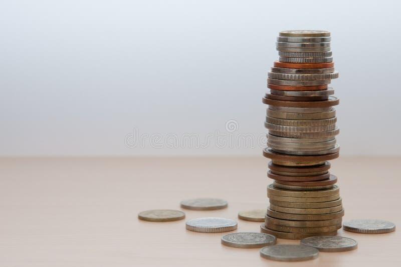 Uma pilha alta de moedas de países diferentes, de cor, de dignidade e de tamanho fotos de stock
