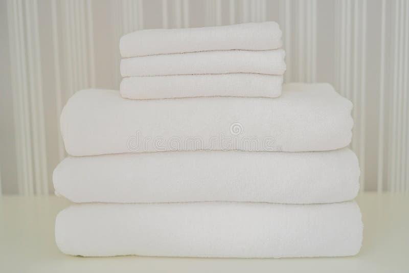 Uma pilha das toalhas macias brancas no armário Serviço no conceito do hotel lavanderia imagem de stock