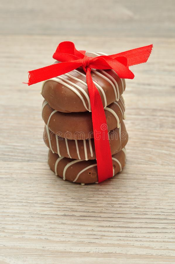 Uma pilha de biscoitos com cobertura em chocolate amarrados com uma fita vermelha imagem de stock