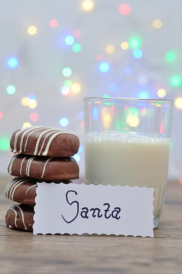 Uma pilha de biscoitos com cobertura em chocolate e de um vidro do leite com uma nota para Santa imagens de stock royalty free
