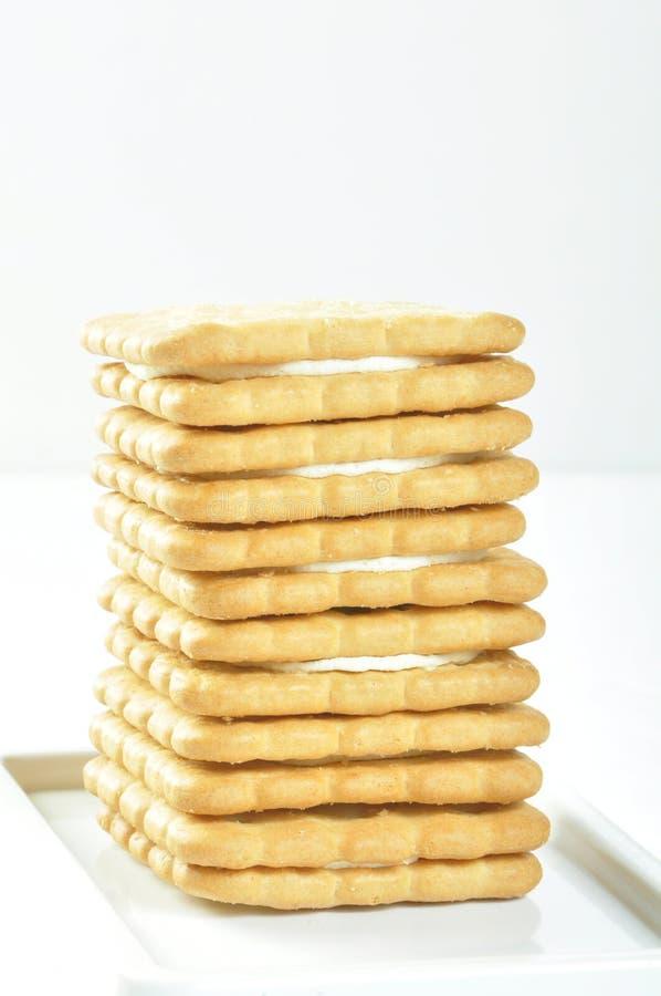 Uma pilha de biscoitos deliciosos do quadrado do trigo com creme no prato branco fotos de stock