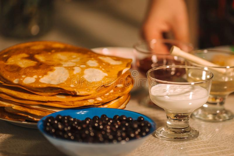 Uma pilha de blini quente das panquecas do russo fino com corintos, mel, creme de leite e doce imagens de stock royalty free