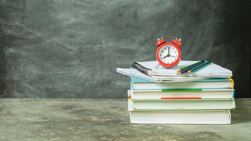 Uma pilha de cadernos educacionais dos livros e de um despertador vermelho no fundo de uma placa de giz Educa??o do conceito imagem de stock royalty free