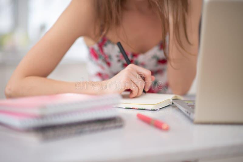 Uma pilha de cadernos na espiral e de estudante no portátil imagens de stock royalty free