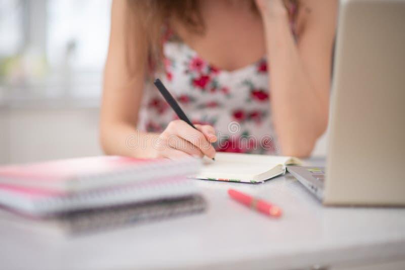 Uma pilha de cadernos na espiral e de estudante no portátil fotografia de stock royalty free