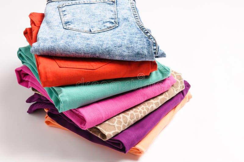Uma pilha de calças de brim coloridas no fundo branco fotografia de stock