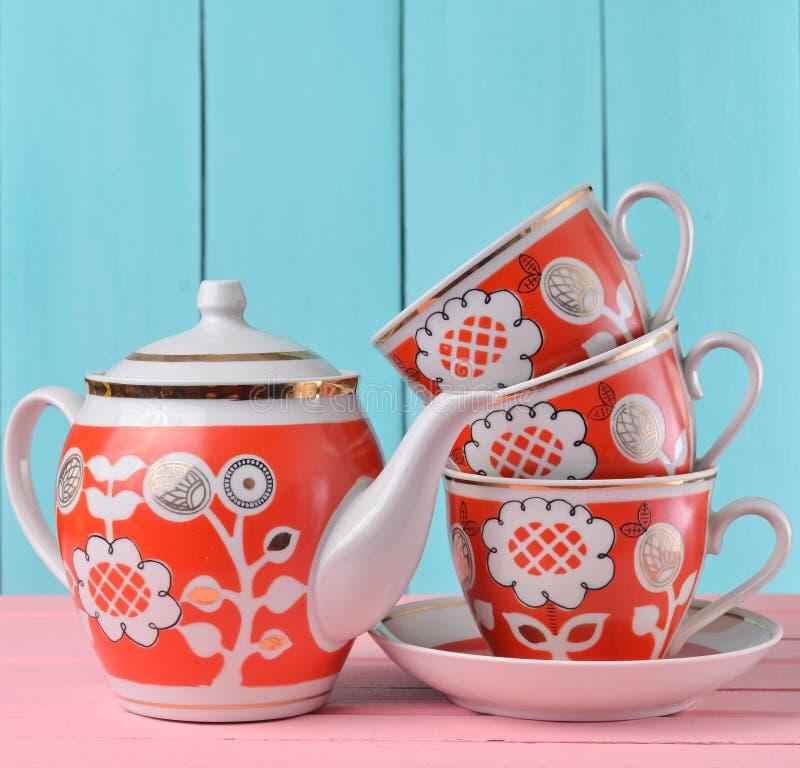 Uma pilha de copos retros cerâmicos com o bule vermelho do patternsand em uma tabela de madeira cor-de-rosa contra um fundo de ma fotos de stock royalty free