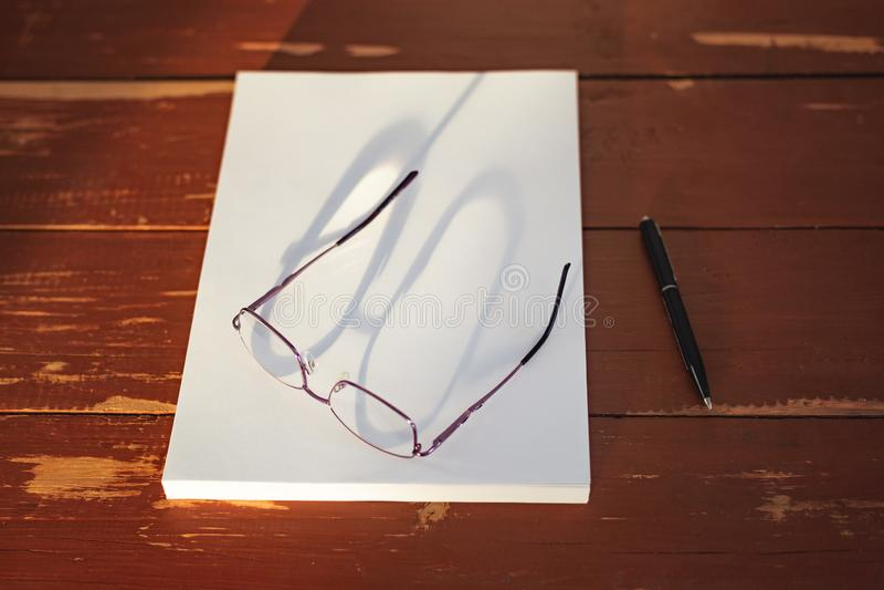 Uma pilha de folhas de papel vazias, uma pena e vidros em uma tabela de madeira vermelha imagem de stock