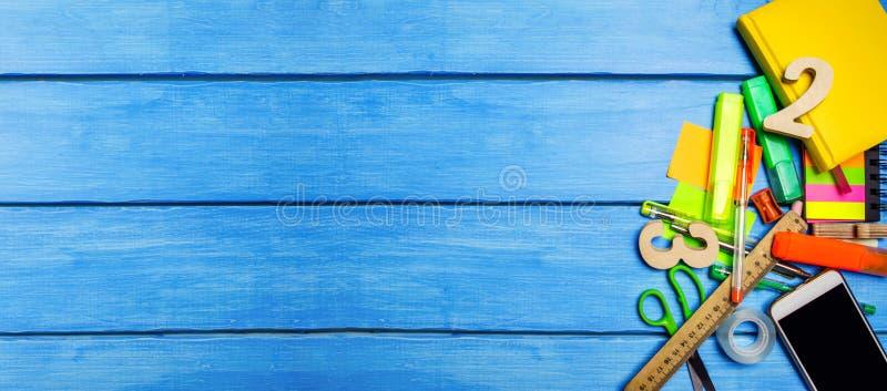 Uma pilha de fontes de escola em um fundo de madeira azul da tabela O conceito do processo educacional, fazendo trabalhos de casa imagem de stock