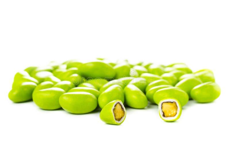 Uma pilha de gumballs verdes com as porcas isoladas em um backgrou branco fotos de stock royalty free
