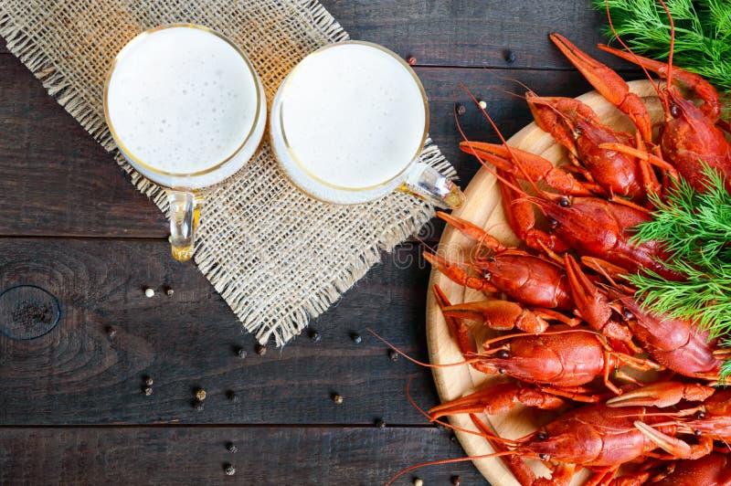 Uma pilha de lagostins fervidos saborosos em uma bandeja de madeira redonda e em dois fotos de stock