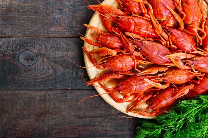 Uma pilha de lagostins fervidos saborosos em uma bandeja de madeira redonda em uma tabela escura Vista superior imagem de stock