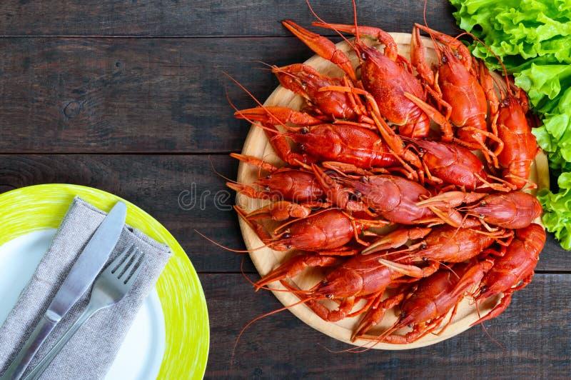 Uma pilha de lagostins fervidos saborosos em uma bandeja de madeira redonda em uma tabela escura Vista superior foto de stock