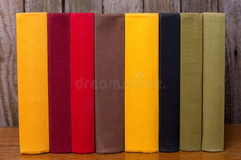 Uma pilha de livros coloridos velhos na tabela Em um fundo de madeira fotos de stock royalty free