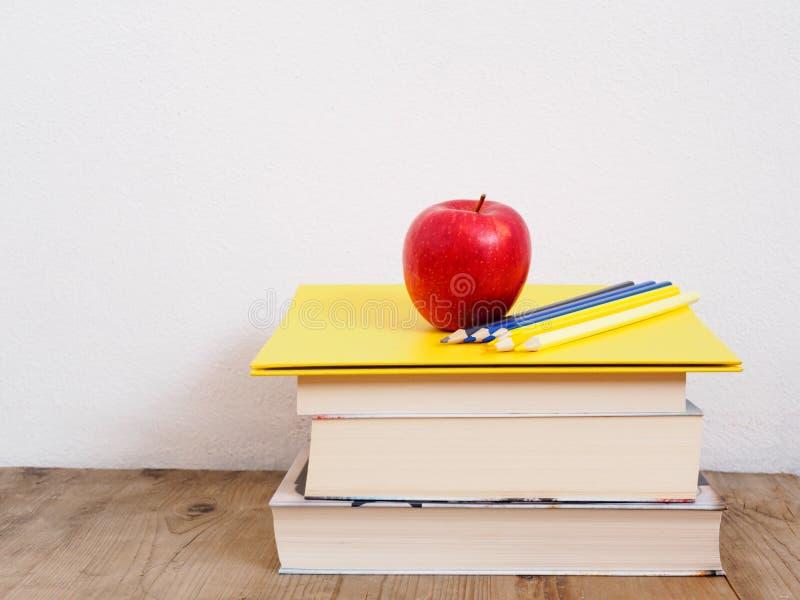 Uma pilha de livros com uma maçã vermelha e uns lápis coloridos imagens de stock