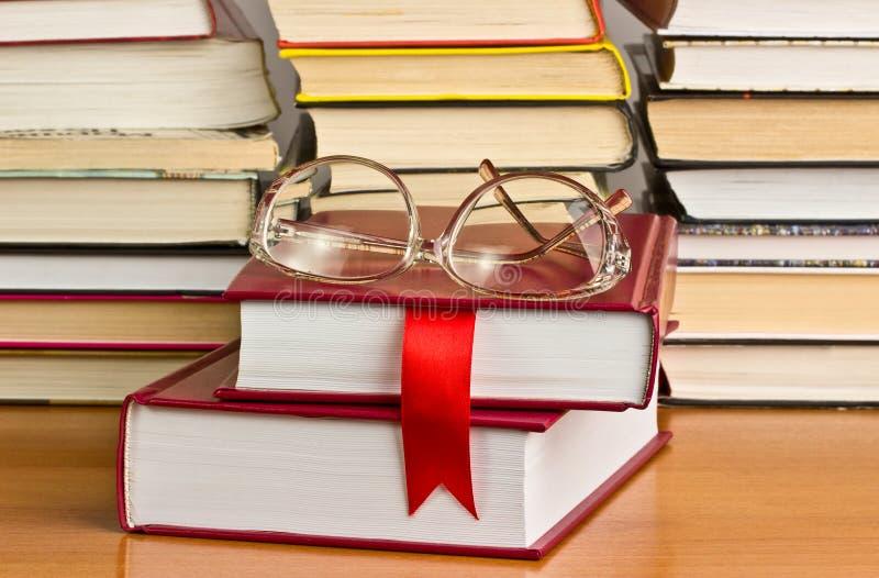 Uma pilha de livros com uma fita vermelha fotos de stock royalty free