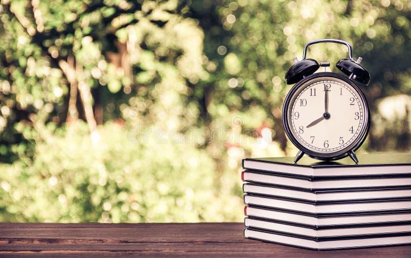 Uma pilha de livros e de um despertador em um verde borrou o fundo Conceito educacional Escola e lições Matização do vintage foto de stock royalty free