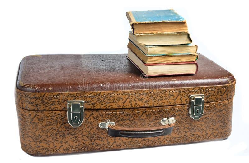 Uma pilha de livros em uma mala de viagem de couro velha isolada em um fundo branco imagem de stock