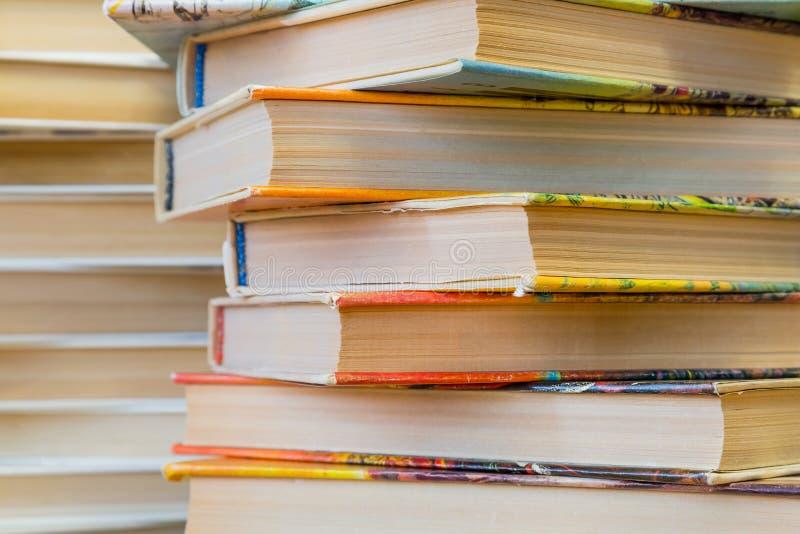 Uma pilha de livros nas tampas coloridos na biblioteca ou na livraria fotos de stock