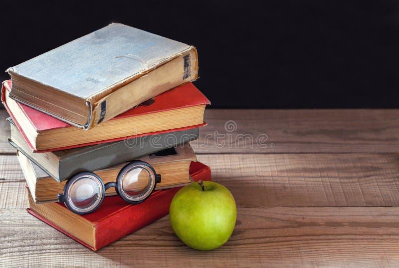 Uma pilha de livros velhos do vintage e de uma maçã verde em uma tabela de madeira rústica imagem de stock royalty free