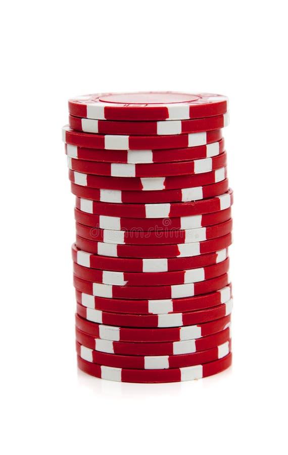 Uma pilha de microplaquetas de póquer vermelhas no branco imagens de stock