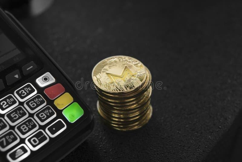 Uma pilha de moedas criptos da moeda de Monero do ouro e de terminal da posição Moneros Cryptocurrency Comércio eletrônico, negóc foto de stock royalty free