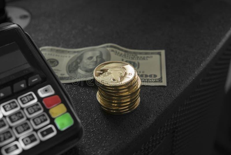 Uma pilha de moedas do titã do ouro e de terminal da posição com uma cédula hindred do dólar em um fundo Titã Cryptocurrency e imagem de stock